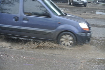 a dirty wave springs from under the wheels of a car