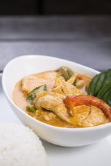 Thai red curry with chicken in white bowl served with rice