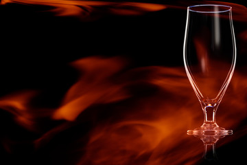 Empty glass of beer in the fire flames.