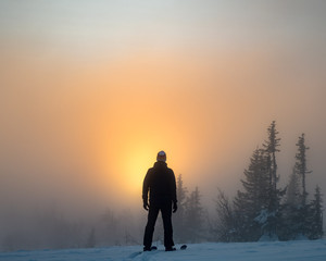 Man standing on top of mountain among golden glow sunset