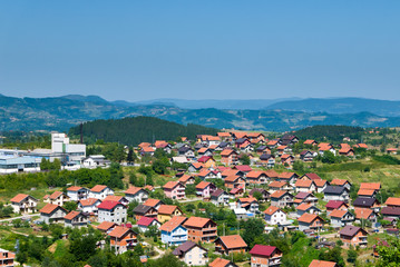 Residential buildings and houses in charming hilly landscape, aerial view