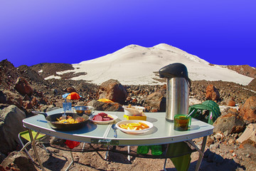 Tourist breakfast. High mountain summit camp located on stony moraine of glacier against the background of high snowy peak under clear blue sky. Early morning.