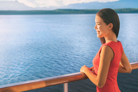 Cruise ship Alaska travel vacation woman on luxury boat. Asian elegant lady looking at sunset view of ocean from balcony deck.