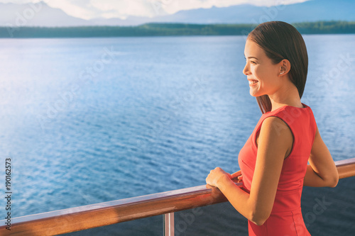 Wall mural Cruise ship Alaska travel vacation woman on luxury boat. Asian elegant lady looking at sunset view of ocean from balcony deck.