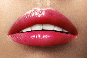 Close-up macro shot of female mouth. Sexy Glamour red lips Makeup with sensuality gesture. Magenta gloss lipstick