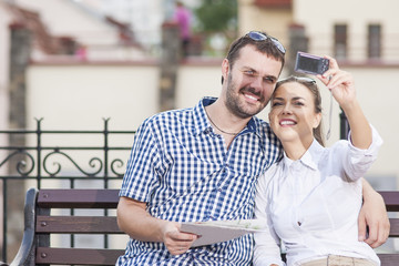 Travel Ideas and Concepts. Young Caucasian Couple in Love Sitting on Bench Outdoors While Taking Selfie Pictures