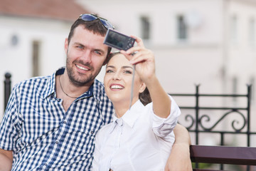 Travel Ideas and Concepts. Young Caucasian Couple in Love Sitting on Bench Outdoors While Taking Selfie Pictures.