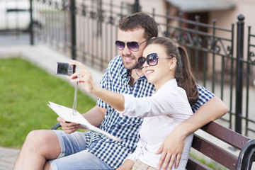 Traveling  Concepts. Young Caucasian Couple in Love Sitting on Bench Outdoors While Taking Selfie Pictures.