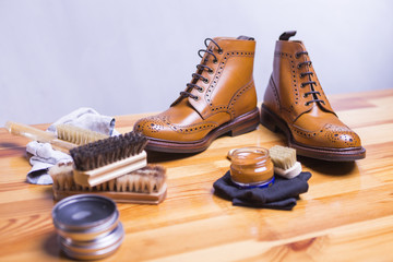 Footwear Ideas and Concepts. Close-up of Premium Tan Brogue Leather Boot with Set of Cleaning Accessories,Wax  and Cloth.Focus on Shoes