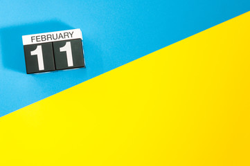 February 11th. Day 11 of february month, calendar on blue and yellow background flat lay, top view. Winter time. Empty space for text