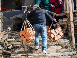 Rear view of an unrecognizable man carring bricks walking on stone steps.