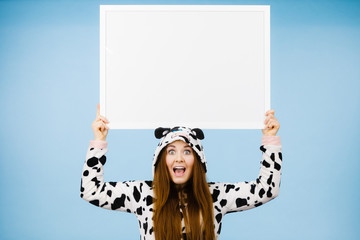 Happy crazy woman in cow costume holding board