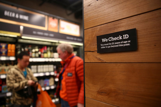 A customer has their identification checked in the beer and wine section of the new Amazon Go store  in Seattle