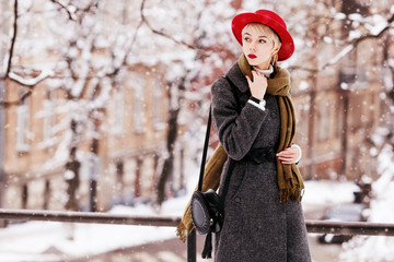 Outdoor portrait of young beautiful girl wearing long grey winter coat, red hat, olive scarf, with small round leather bag. Model walking in street of european city. Snowfall. Copy, empty space