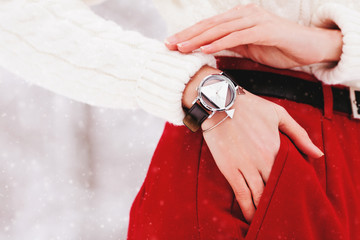 Close up photo of metallic silvery wrist watch with wide black leather bracelet. Model posing in street, wearing winter white sweater and red high-waisted pants. Copy, empty space for text