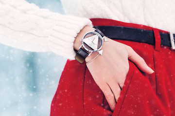 Close up photo of elegant silver wrist watch with geometric design, wide black leather bracelet. Model posing in street, wearing winter white sweater, red pants. Snowfall. Toned. Copy, empty space