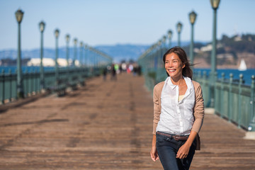 San Francisco travel lifestyle woman walking happy on pier. Asian girl smiling relaxing in harbor city in USA.
