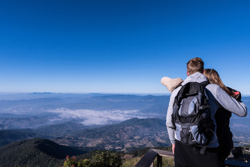 Hikers with backpack on top of a mountain and enjoy the view of the blue sky