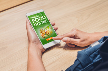 People order food online with mobile apps on wood table at home,online food delivery technology in daily lifestyle,Digital age concept.