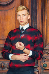 Young blonde American male college student wearing patterned red, black knit sweater, glasses hanging on collar, standing by brown vintage wooden office door, confidently looking at you..
