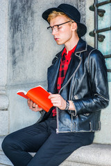 Way to Success. Young American college student studying in New York, wearing black leather jacket, red patterned shirt, black hat, glasses, sitting against vintage wall on campus, reading red book..