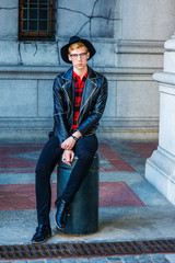 Young Man Casual Spring/Autumn Fashion in New York, wearing black leather jacket, patterned red undershirt, pants, leather shoes, hat, glasses, sitting on metal pillar on vintage street, relaxing..