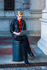 Young blonde American Man studying, working in New York, wearing black leather jacket, pants, leather shoes, sitting on metal pillar on vintage street, reading, working on laptop computer..