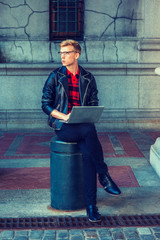 Young blonde American Man studying, working in New York, wearing black leather jacket, pants, leather shoes, sitting on metal pillar on street, working on laptop computer, looking away, thinking..