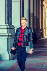 Young blonde American Man traveling, working in New York, wearing black leather jacket, red patterned shirt, carrying shoulder bag, holding laptop computer, walking through narrow vintage street..