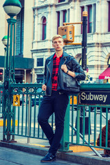 Young blonde American Man traveling in New York, wearing black leather jacket, red patterned shirt, pants, leather shoes, carrying bag over shoulder, standing on street by Subway sign, waiting..
