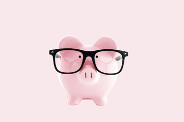 Piggy bank in in glasses  on pastel pink background