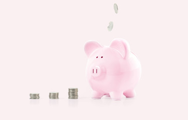 Female hand putting coin into piggy bank on pastel pink background