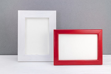 red and white photo frames against grey wall background