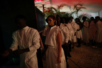 Models wearing creations from Mawussia Opont await to parade during the show at the Haiti Fashion Week in Port-au-Prince