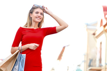 Young smiling woman with shoping bags looking ahead