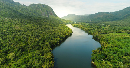 Aerial view of river in tropical green forest with mountains in background Fototapete