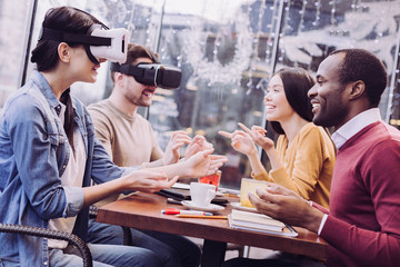 Virtual universe. Gay pleasant two friends trying VR headsets and resting at cafe while laughing