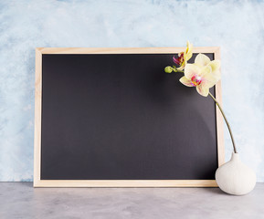 Back chalkboard mockup with yellow orchid in vase. Business, interior design, lettering concept. Text space