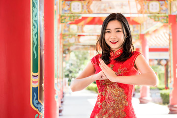 Asian woman in traditional red dress making salute