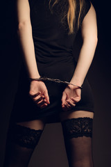 Woman in handcuffs. BDSM concept. Adult role game concept at night