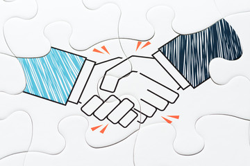 Handshake jigsaw puzzle pieces. Concept image of agreement and corporation.