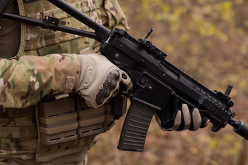 close up picture of black assault rifle in hands of nato soldier