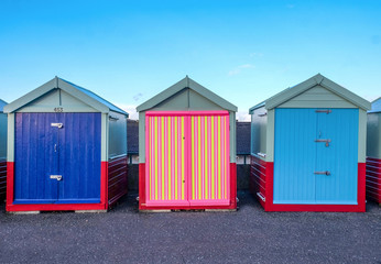 a line of three beach huts on Brighton promenade 2 beach huts are blue and one is multi coloured stripey yellow, pink, colours, standing out from the rest