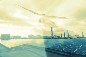 Renewable energy concept. Double exposure of Wind mill and factory buildings.