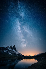 Spoed Fotobehang Nachtblauw Beautiful view of milky way glowing on the sky with mountains and river and reflections of stars