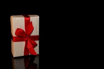 красивый подарок перевязанный красной лентой на черном фоне