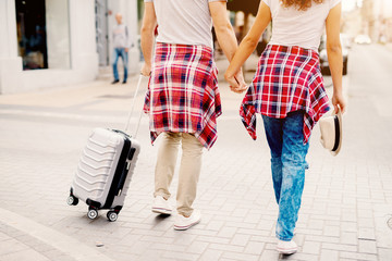 Couple holding hands while walking thru the city on a vacation time.