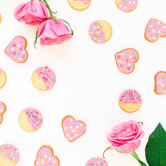 Cookies with pink glaze and roses on white background. Love composition. Flat lay. top view.
