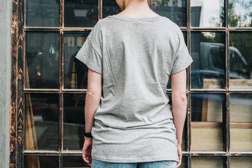 Summer day. Front view. Young millennial woman dressed in gray t-shirt is stands against window. Mock up. Space for logo, text, image.