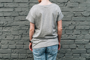 Summer day. Back view. Young millennial woman dressed in gray t-shirt is stands against gray brick wall. Mock up. Space for logo, text, image.